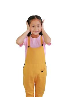 Kleines asiatisches mädchen, das ohren mit beiden händen schließt, hörgeräusche vermeiden. kind, das seine ohren mit dem blick lokalisiert auf weißem hintergrund bedeckt.