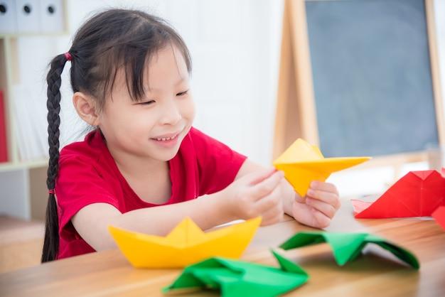 Kleines asiatisches mädchen, das papierflugzeug vom papierfalten in der schule tut.