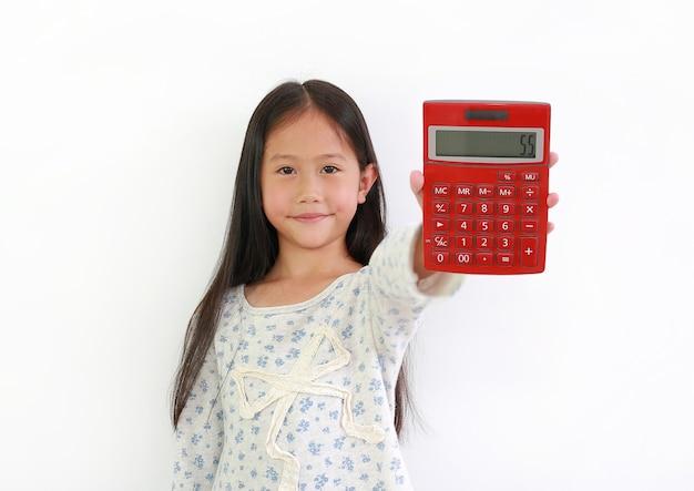 Kleines asiatisches mädchen, das rechner auf weißem hintergrund zeigt. kind hält einen roten taschenrechner