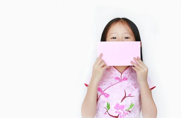 Kleines asiatisches mädchen, das rosa umschlagpaket des chinesischen neujahrsfests auf ihrem mund hält.