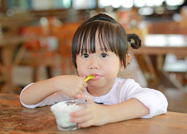 Kleines asiatisches mädchen, das selbst gemachte eiscreme in der schale isst