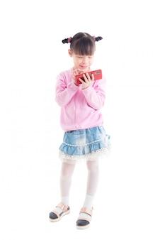 Kleines asiatisches mädchen, das spiele am intelligenten telefon mit lächeln über weißem hintergrund steht und spielt