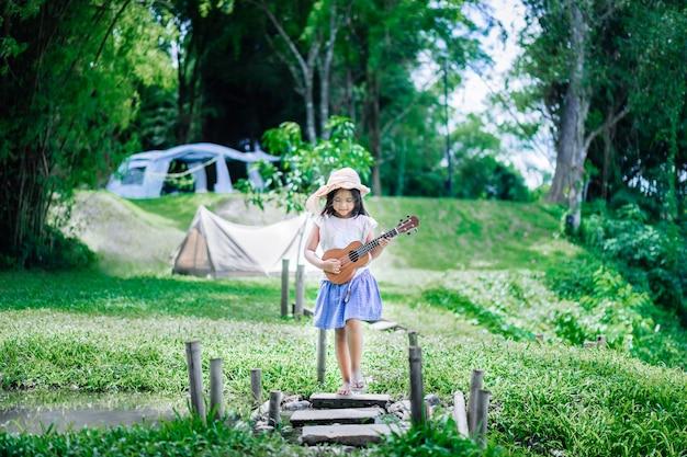 Kleines asiatisches mädchen, das ukulele oder hawaiianische gitarre im park spielt, während im sommer kampiert