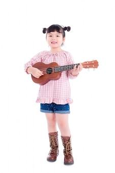 Kleines asiatisches mädchen, das ukulele über weißem hintergrund spielt