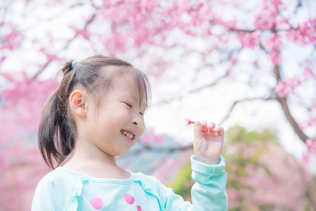 Kleines asiatisches mädchen, das vor kirschblüte-baum lächelt.