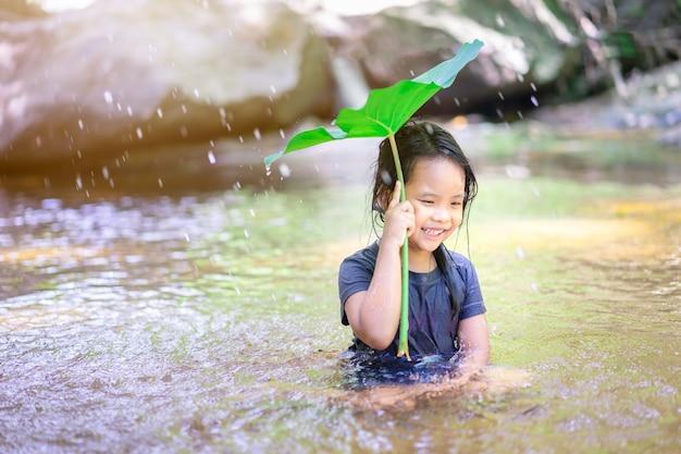 Kleines asiatisches mädchen, das wasser unter lotosblatt im wasserfall sitzt und spielt