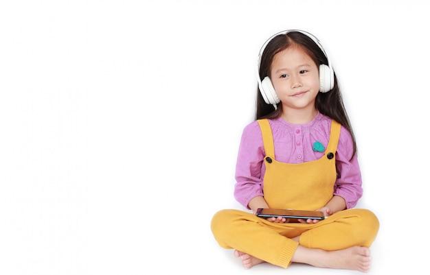 Kleines asiatisches mädchen des porträts genießt, musik durch kopfhörer zu hören