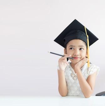 Kleines asiatisches mädchen des porträts trägt den absolventhut, der das sitzende denken des bleistifts etwas und lächeln mit glück hält