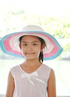 Kleines asiatisches mädchen draußen im sommerhut