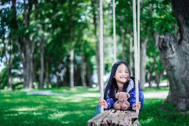 Kleines asiatisches mädchen im prinzessinnenkostüm, das bär auf hölzerner schaukel im park spielt