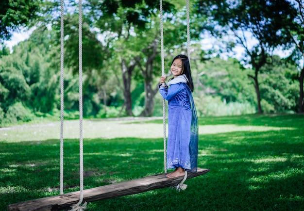 Kleines asiatisches mädchen im prinzessinnenkostüm, das hölzerne schaukel im park spielt