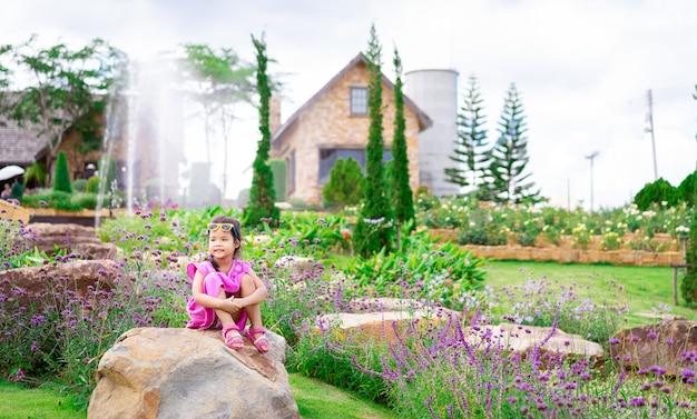 Kleines asiatisches mädchen im rosa kleid, das auf dem felsen im blumengarten sitzt