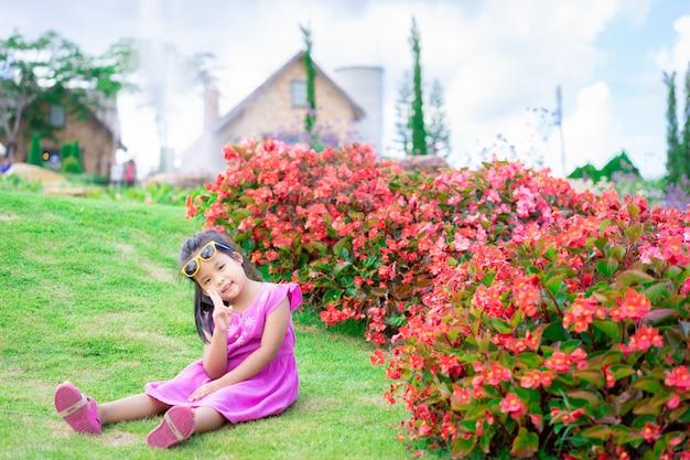 Kleines asiatisches mädchen im rosa kleid, das aus den grund im blumengarten sitzt
