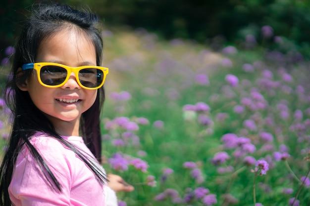Kleines asiatisches mädchen im rosa kleid, das die sonnenbrille trägt, die im lila blumengarten steht