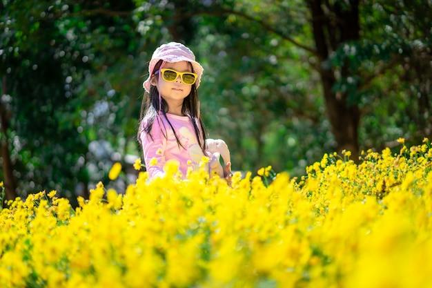 Kleines asiatisches mädchen im rosa kleid tragen hut und sonnenbrille, die im gelben blumengarten stehen