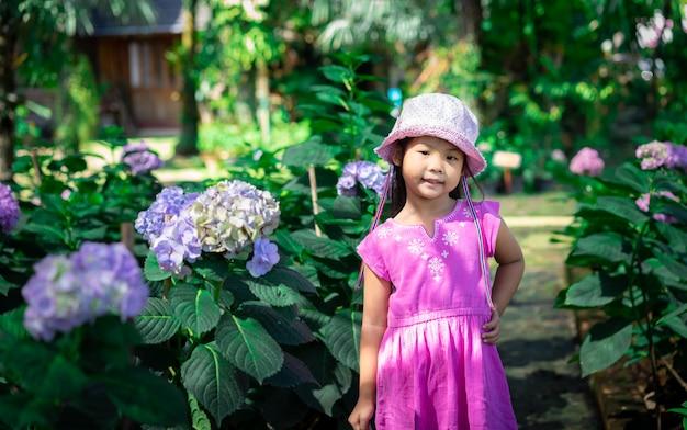 Kleines asiatisches mädchen im rosa kleid und im hut, die im blumengarten steht