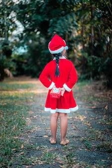 Kleines asiatisches mädchen im roten weihnachtsmannkostüm treten mit geschenkbox im park zurück