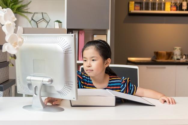 Kleines asiatisches mädchen mit laptop. bildungskonzept.