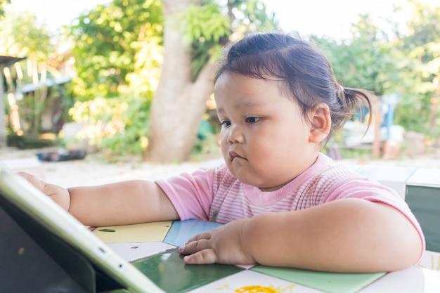 Kleines asiatisches mädchen sitzt beim betrachten des digitalen tablets. es lernt für moderne kinder, aber es kann sich negativ auf die augen und reflexe der kinder auswirken.