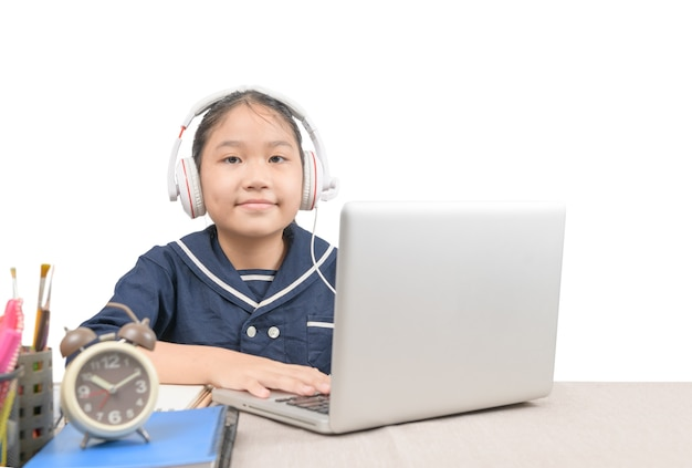 Kleines asiatisches mädchen tragen kopfhörer und machen hausaufgaben mit laptop online isoliert