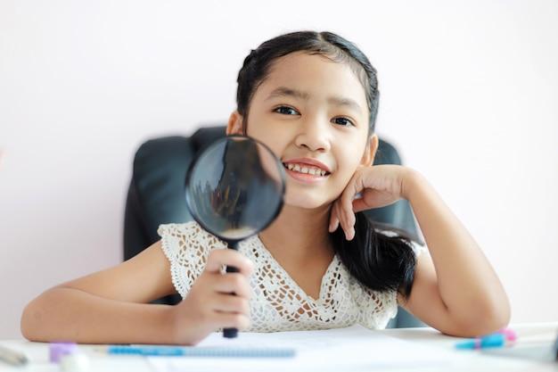 Kleines asiatisches mädchen, welches das vergrößerungsglas tut hausarbeit und lächelt mit glück für flache schärfentiefe des ausgewählten fokus des bildungskonzeptes verwendet