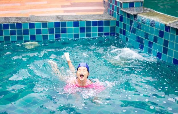 Kleines asiatisches mädchen, welches die aufblasbaren ärmel spielen im pool trägt