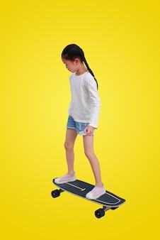 Kleines asiatisches mädchenkind, das auf einem skateboard lokalisiert auf gelbem hintergrund eisläuft. kind reitet auf skateboard mit beschneidungspfad