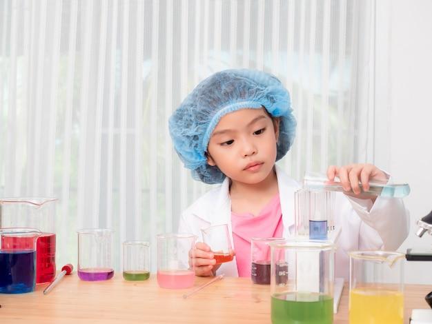 Kleines asiatisches nettes mädchen 6 jahre alte rolle, die einen wissenschaftler im wissenschaftslabor mit ausrüstung und chemikalien spielen.