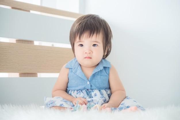 Kleines asiatisches nettes mädchen, das auf bett im schlafzimmer sitzt