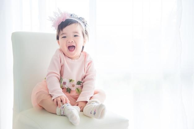 Kleines asiatisches nettes mädchen, das sitzt und lächelt auf dem stuhl