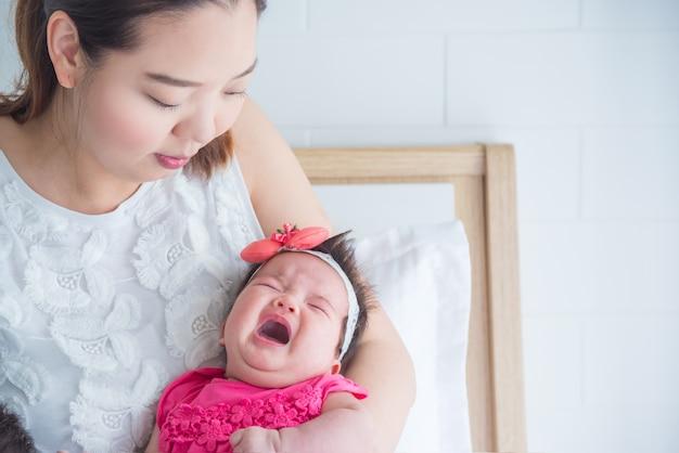 Kleines asiatisches neugeborenes schreien während mutter, die im schlafzimmer hält