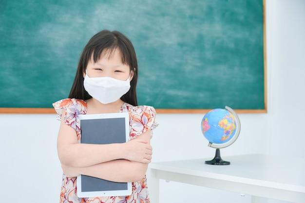 Kleines asiatisches schulmädchen, das fcial maske steht, die im klassenzimmer an der schule steht.