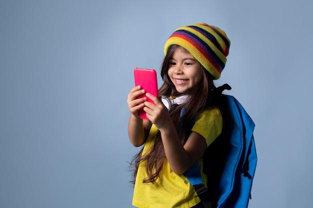 Kleines asiatisches schulmädchen, das ihr telefon überprüft