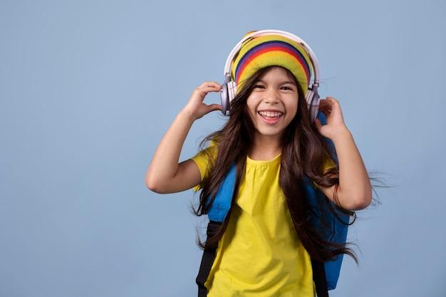 Kleines asiatisches schulmädchen, das musik über kopfhörer hört