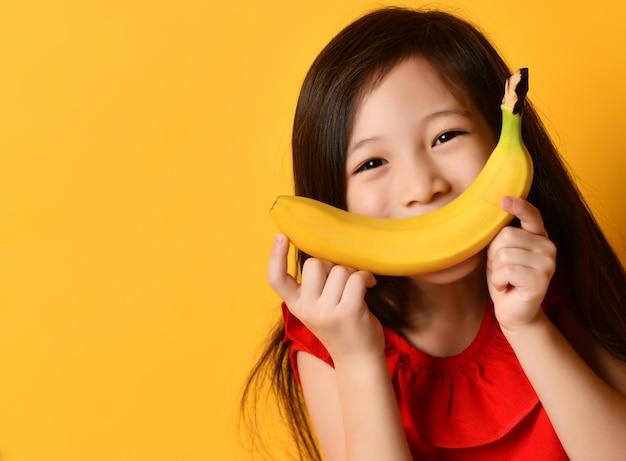 Kleines asiatisches schulmädchen in der roten bluse. sie brachte banane an ihren mund, als wäre es ihr lächeln, das auf orangefarbenem studiohintergrund posierte. kindheit, früchte, emotionen, werbung. nahaufnahme, platz kopieren