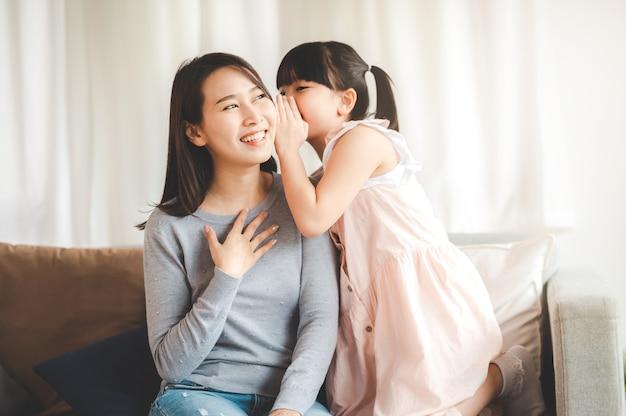 Kleines asiatisches tochtermädchen, das der glücklichen lächelnden mutter im wohnzimmer ein geheimnis zuflüstert