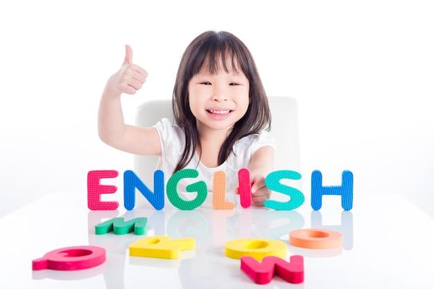 Kleines asiatisches vorschulmädchen, das englisches wort durch ihr spielzeug über weißem hintergrund macht