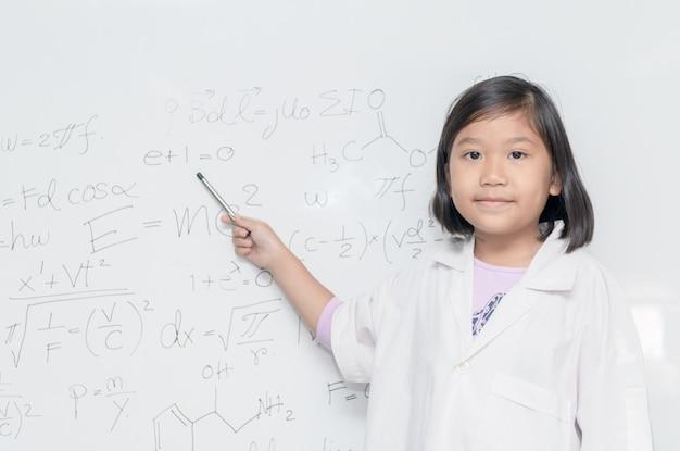Kleines asiatisches wissenschaftlermädchen, das auf weißes brett zeigt