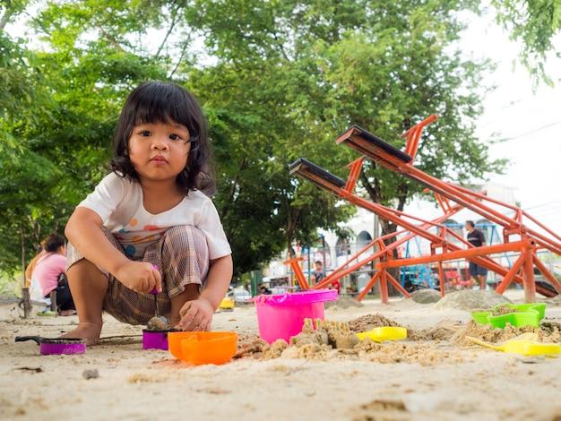 Kleines asien-mädchen, das im sandkasten sitzt und mit spielzeugsand-schaufeleimer spielt