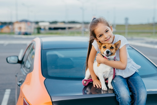 Kleines attraktives weibliches kind umfasst ihren lieblingshund, sitzt zusammen am kofferraum des autos