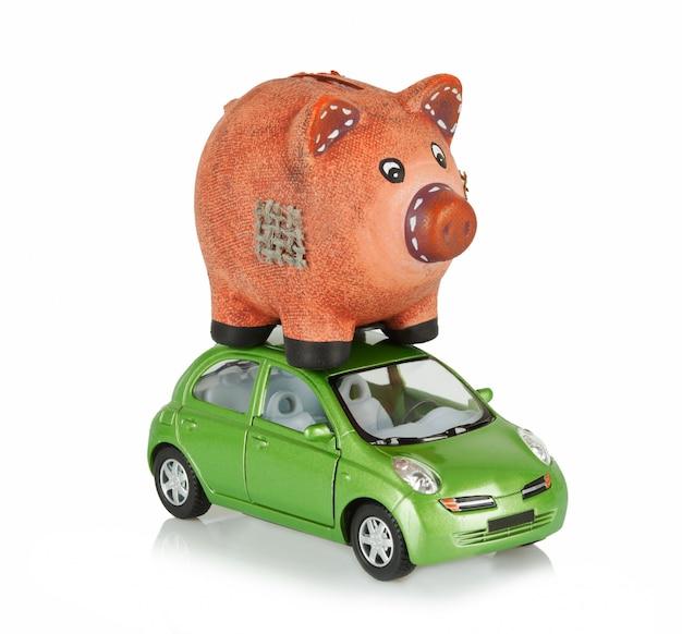 Kleines auto mit sparschwein auf dem dach.