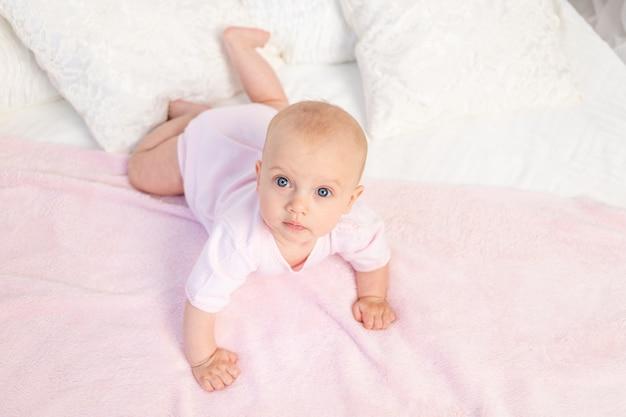 Kleines baby 6 monate alt, das auf einem weißen und rosa bett zu hause kriecht und wegschaut, draufsicht, platz für text