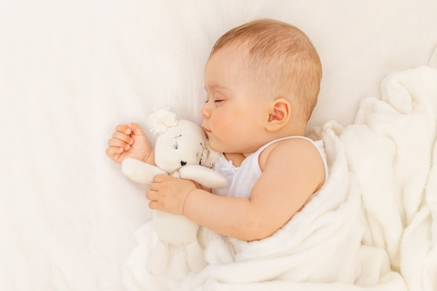 Kleines baby 6 monate alt, das in einem weißen bett schläft