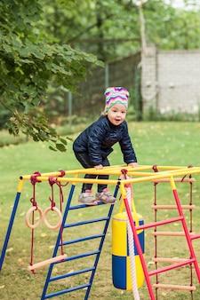 Kleines baby, das am spielplatz im freien spielt