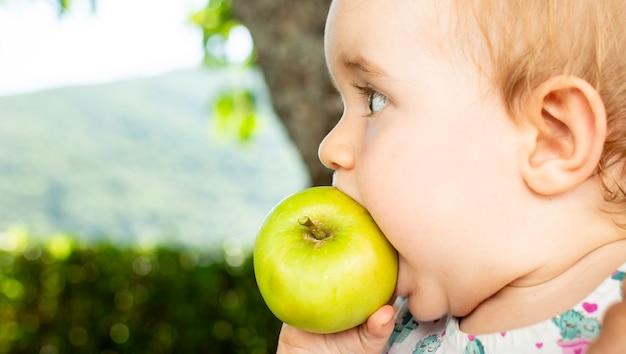 Kleines baby, das apfel isst