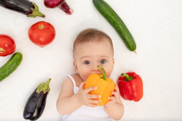 Kleines baby, das auf dem bett mit gemüse sitzt