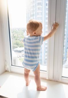 Kleines baby, das auf der fensterbank steht und den fenstergriff zieht, konzept von kindern in gefahr