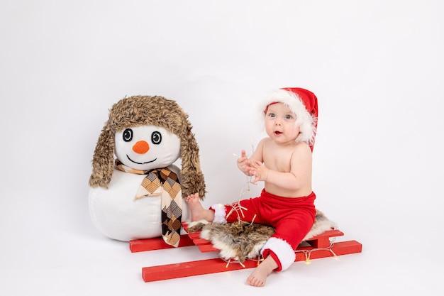 Kleines baby, das auf einem roten schlitten in einer weihnachtsmannmütze auf einem weißen isolierten hintergrund mit einem schneemann sitzt