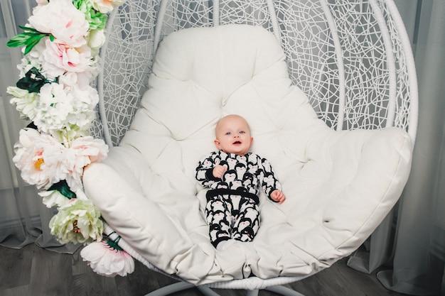 Kleines baby, das auf einem runden schwingen und einem lächeln liegt