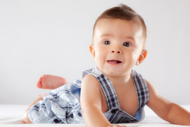 Kleines baby, das auf einem weißen hintergrund lächelt.